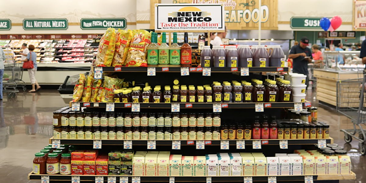 The taste the tradition program stand is shown in a grocery store. Many New Mexico made products are shown on the stand.