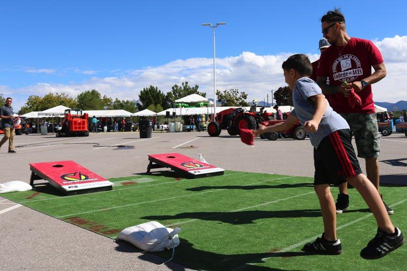 Boy plays bean-bag toss outdoors on turf, man observes