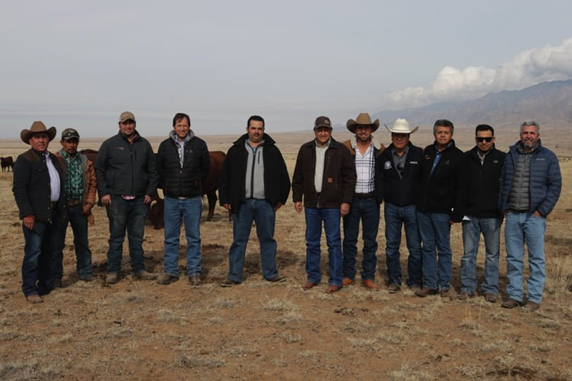 A group of men standing in a row on rangeland with mountains and clouds in background.