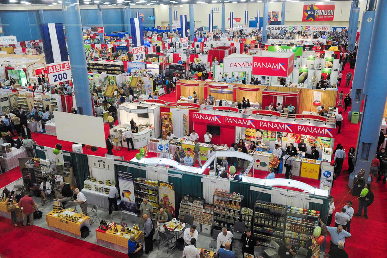 A bird's eye view is shown of a food show. There are several aisles set-up with many food items and brands positioned in front and around the stands. Many people are gathered around each booth.