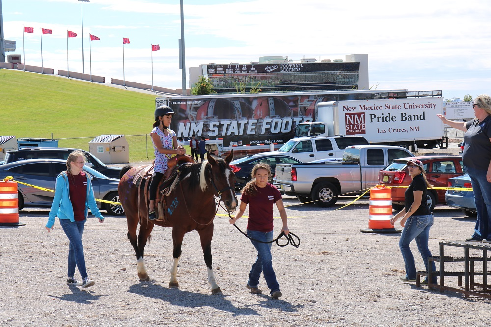 The NMSU Therapeutic Riding Program hosted horse rides as an interactive exhibit to young Aggie fans at AG Day 2018.