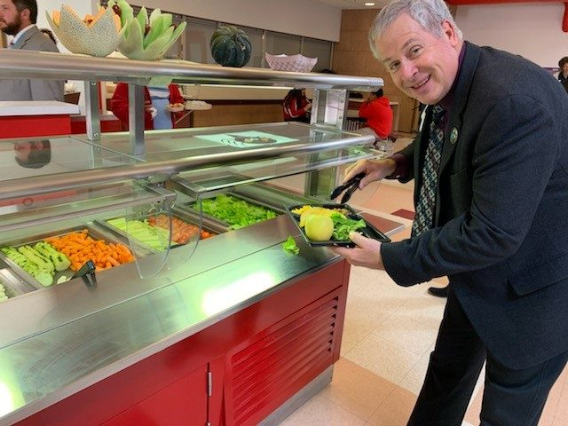 Man serving vegetables onto his plate in cafeteria