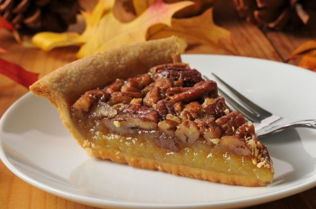 A slice of pecan pie on a colorful holiday table