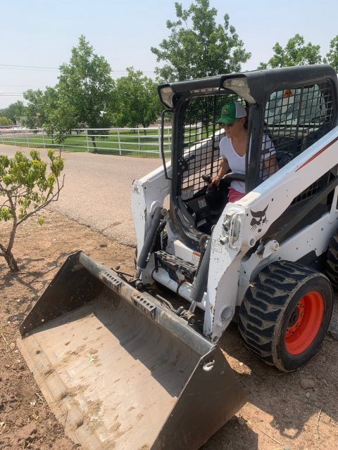 A young woman moves dirt with a front-end loader on a farm with trees in background