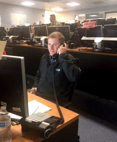 Man in black jacket sitting in communications room looking at computer screen with phone held to his hear