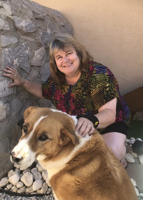 Smiling woman kneeling down with one hand on rock wall and one hand on back of brown and white dog