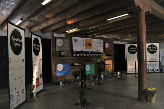 Several agriculture-related displays on wooden wall and standing on concrete floor