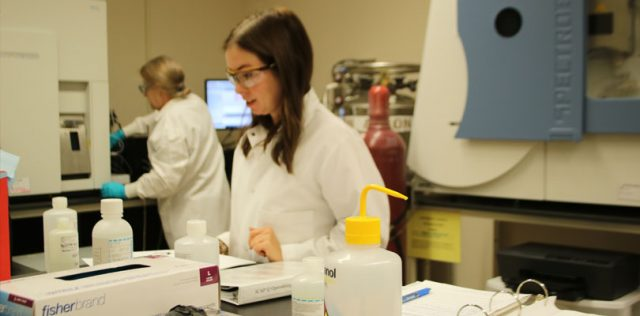 Women in white lab coat and safety classes in chemistry lab, with another women in lab coat and safety glasses and gloves in background