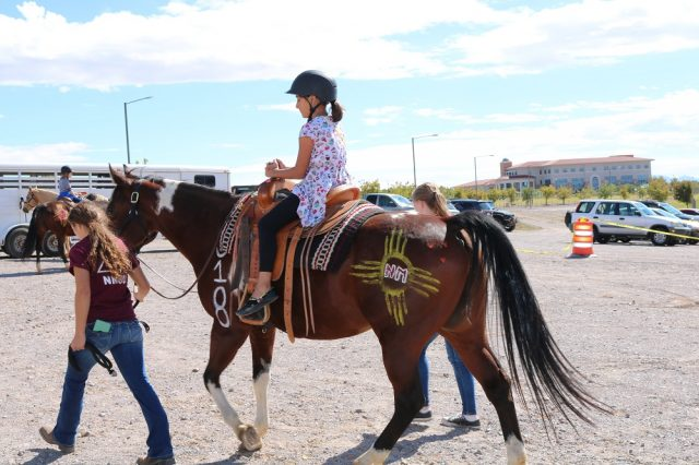 New Mexico State University female student leads a brown horse ridden by a young girl at a previous AG Day