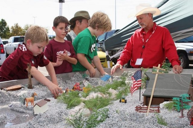 Three young boys interact with sand and water display, while man in red shirt explains interactive water conservation display